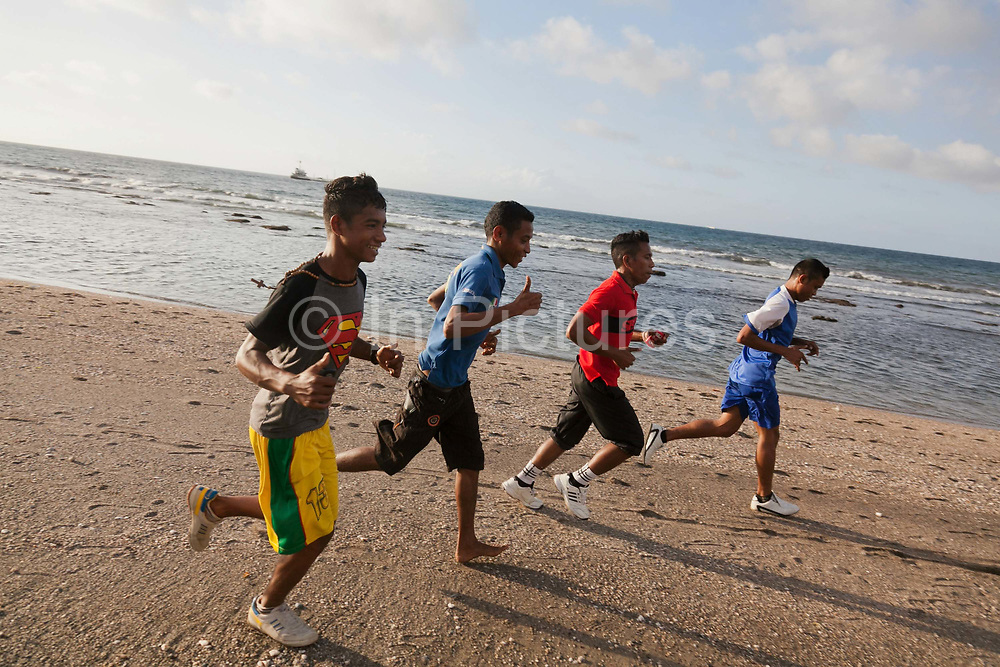 Young men running along the beach in Dili, Timor Leste. Timor Leste has a very young population and many young men train and keep fit. After lots of internal conflict there are now servere restrictions on any practise of martial arts, a chosen past time for gangs in recent past.
