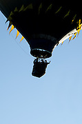 A black hot air balloon with yellow flags is silhouetted against a clear blue sky, Crown of Maine Balloon Fair, Presque Isle, Maine.
