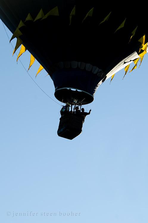A black hot air balloon with yellow flags is silhouetted against a clear blue sky, Crown of Maine Balloon Fair, Presque Isle, Maine.