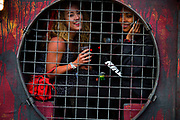Glastonbury Festival, 2015.<br /> two girls sitting in caged window of Greenpeace bar, one of them using her mobile phone