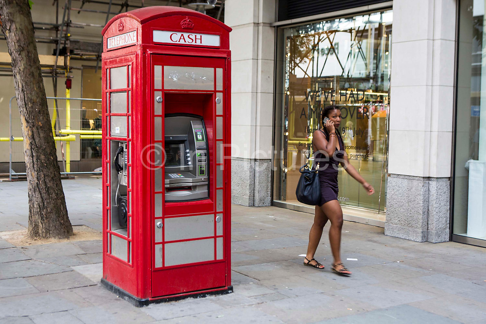 A woman on a mobile phone walks past a traditional British red phone box on Duke of York Square, London.  This telephone box has been adapted to include a banking ATM cash machine. The red phone box is often seen as an iconic British symbol throughout the world, although the numbers of these phone boxes in service are rapidly decreasing with the rise of mobile cell phones.