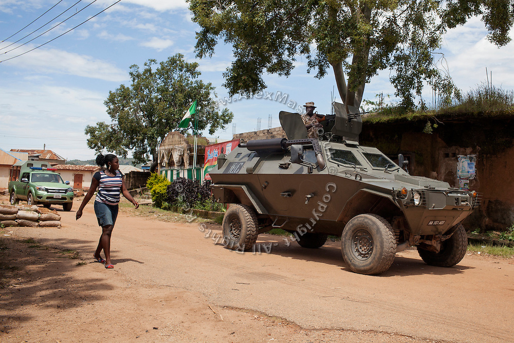 A Christian woman is walking by an armoured truck providing security for the Christian Catholic Cathedral Of Our Lady Fatima in Jos, Plateau State, Nigeria.