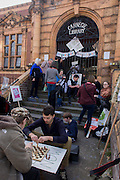 Campaigners protesting about the closed Carnegie Library play chess outside, in Herne Hill, south London on 2nd April 2016. The angry local community in the south London borough have occupied their important resource for learning and social hub for the weekend. After a long campaign by locals, Lambeth have gone ahead and closed the library's doors for the last time because they say, cuts to their budget mean millions must be saved. A gym will replace the working library and while some of the 20,000 books on shelves will remain, no librarians will be present to administer it. London borough's budget cuts mean four of its 10 libraries will either close, move or be run by volunteers. (Photo by Richard Baker / In Pictures via Getty Images).
