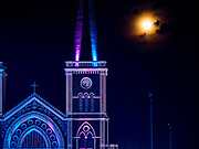 "23 DECEMBER 2018 - CHANTABURI, THAILAND: The full moon behind the cathedral in Chantaburi. Cathedral of the Immaculate Conception is holding its annual Christmas festival, this year called ""Sweet Christmas @ Chantaburi 2018"". The Cathedral is the largest Catholic church in Thailand and was founded more than 300 years ago by Vietnamese Catholics who settled in Thailand, then Siam.   PHOTO BY JACK KURTZ"