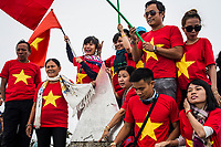 Travelers pose with Vietnamese flags at the top of Mount Fansipan, the highest mountain in Indochina.
