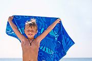 A boy holds a towl while standing in front of the ocean.