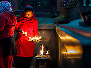 07 MARCH 2017 - KATHMANDU, NEPAL: A woman carries a tray of prayer candles at the Kamaladi Ganesh Temple, the most important Hindu temple dedicated to Ganesh, known as the overcomer of obstacles, in Kathmandu. In Hindu theology, Tuesdays are the best day to pray to Ganesh and the temple is very busy on Tuesdays. People frequently visit temples dedicated to Ganesh when they buy a new home or start a new job.     PHOTO BY JACK KURTZ