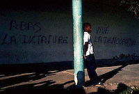 "February 1986, Haiti --- A Haitian boy leans on a green post.  Behind him is graffiti, ""down with the dictator"" and ""long live democracy"". --- Image by © Owen Franken/CORBIS"
