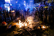 Riot police officers surround fire which is made by protesters on September 6th, 2019 near Mong Kok Police Station in Hong Kong, China.