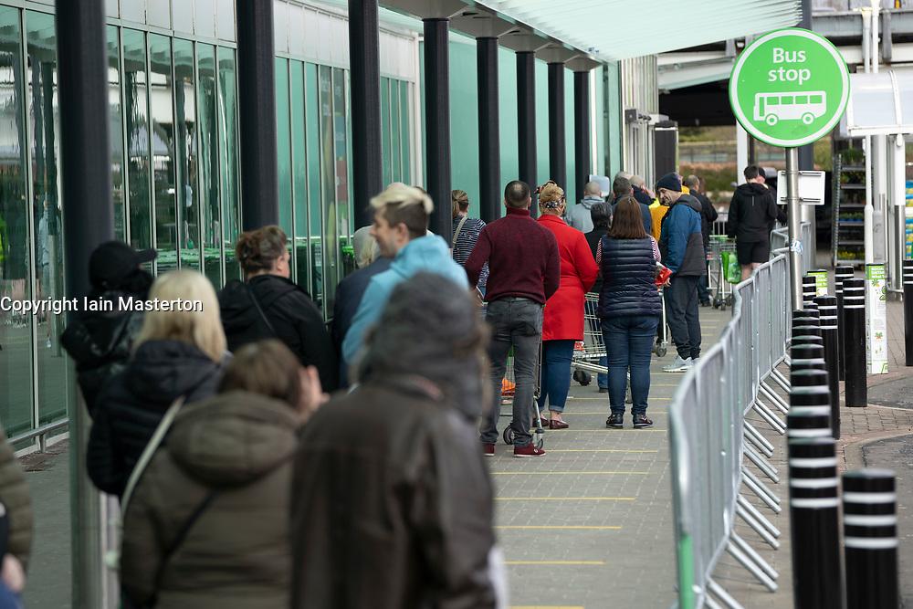 Hamilton, Scotland, UK. 1 April, 2020. Long queue of shoppers at Asda in Hamilton maintaining recommended coronavirus social distancing. Iain Masterton/Alamy Live News