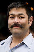 A close-up portrait of a young man in his thirties street portrait with moustache. Born in Hawaii, the man is of Asian descent and his minimal moustache shows the limited growth on his face although he is clean shaven, with a smooth chin. The moustache turns upwards slightly in a rather cheeky style.