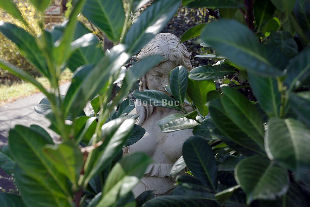 statue of a nude female person hiding in the bush