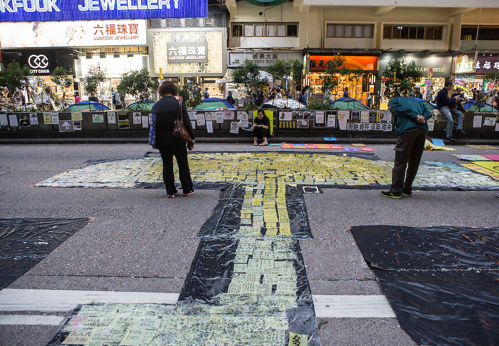 Looking at signs of support that have been laid out in the shape of an umbrella, the symbol of the ongoing protests in Hong Kong. Protesters known as the Umbrella Revolution or Occupy Mongkok, an extension of the larger Occupy Central movement, have taken over a number of blocks on the busy road and staged an ongoing demonstration calling for universal suffrage for Hong Kong.