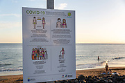 A sign with Covid-19 rules stands in front of a deserted beach in Puerto del Carmen, Lanzarote, Spain on 21st November 2020. Beaches and resorts across the island are nearly deserted since tourism plummeted due to Covid restrictions elsewhere in Europe. Although the Canary Islands have been relatively unscathed by the virus, with 155 lives lost from 2.1 million residents, the region is heavily dependent on tourism and locals are hoping that numbers recover as lockdown measures ease and vaccines potentially reduce the numbers of infections.