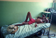 Elderly lays in bed at hospital in Ouanaminthe, Haiti.