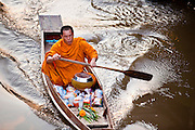 """10 JULY 2011 - AMPHAWA, SAMUT SONGKRAM, THAILAND:   A Buddhist monk from Wat Amphawan Chetiyaram in Amphawa, Thailand, about 90 minutes south of Bangkok, approaches a home on the main canal during his alms round. Most of the monks from the temple use boats to go from house to house on their alms rounds. The Thai countryside south of Bangkok is crisscrossed with canals, some large enough to accommodate small commercial boats and small barges, some barely large enough for a small canoe. People who live near the canals use them for everything from domestic water to transportation and fishing. Some, like the canals in Amphawa and nearby Damnoensaduak (also spelled Damnoen Saduak) are also relatively famous for their """"floating markets"""" where vendors set up their canoes and boats as floating shops.      PHOTO BY JACK KURTZ   PHOTO BY JACK KURTZ"""