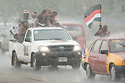 Supporters of the National Democratic Congress (NDC), Ghana's official opposition party, ride in the back of a pick-up truck during a downpour as they arrive at a rally in Tema, roughly 30km east of Ghana's capital Accra on Friday December 5, 2008. Ghanaians are voting in a presidential election on December 7 as incumbent John Agyekum Kufuor, leader of the New Patriotic Party (NPP),  is to step down after ruling for 2 consecutive 4-year terms.