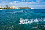 Aerial view of a woman surfing off of Waikiki Beach, Honolulu, Oahu, Hawaii