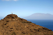 One hiker waives in the top of a hill on Brava's east coast. On the background massive Fogo island is omnipresent with its 2829 metres vulcano.
