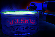 "A can opener has partially removed the lid on a can labeled ""Fukushima - Solid White Albacore"" and the contents revealed are glowing a sickly green color.Black light"