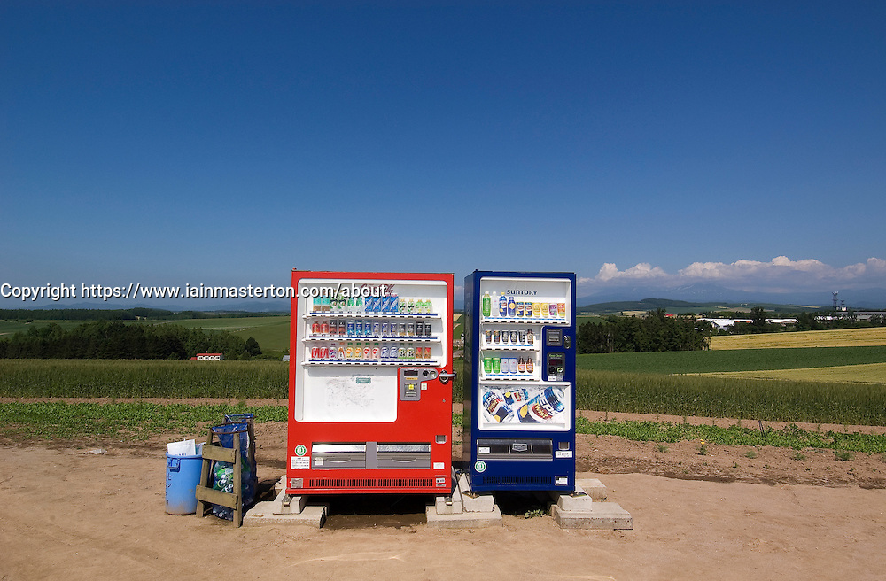 Soft drink vending machines contrast with the countryside of Hokkaido in Japan