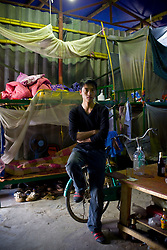 A young Chinese worker from Guangxi province rests at the dorm near the Haiphong Thermal Power Plant construction site in Trung Son, Vietnam, Nov. 22, 2009. At the construction site here, a few miles northeast of the port city of Haiphong, an entire Chinese world has sprung up, including four walled dormitory compounds for the Chinese workers, restaurants with Chinese signs advertising dumplings and fried rice, and currency exchange shops.