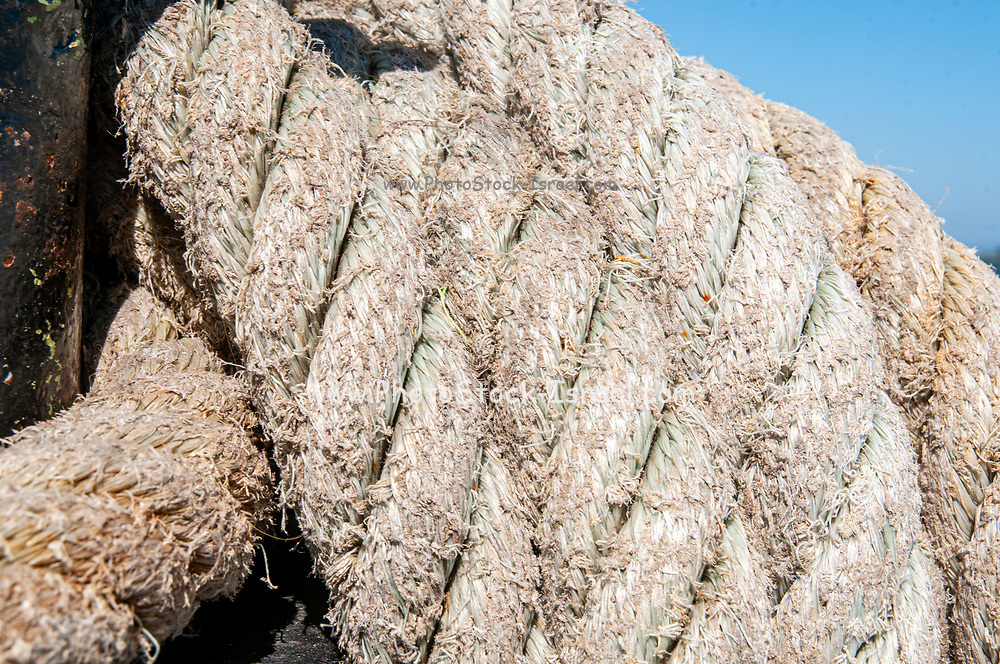 Weathered rope wrapped around a bollard on a ferryboat