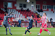 Morecambe midfielder John O'Sullivan (16) chases the ball as Stevenage midfielder Romain Vincelot (4) and Stevenage forward Aramide Oteh (28) close him down as Stevenage goalkeeper David Stockdale (37) comes to collect the ball during the EFL Sky Bet League 2 match between Stevenage and Morecambe at the Lamex Stadium, Stevenage, England on 6 February 2021.