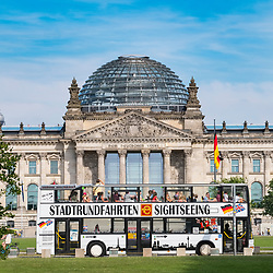 Tourist sightseeing city bus tour passes the German Reichstag parliament building in Berlin Germany