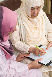 Young female carer helping older woman fill out a housing benefit form,