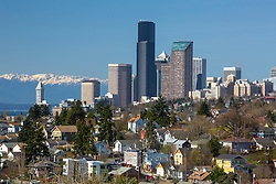 North America, United States, Washington, Seattle. A Seattle neighborhood and the downtown skyline, with the Olympic Mountains in the background. The Smith Tower is the building on the far left, and the Columbia Center is the tall black building.
