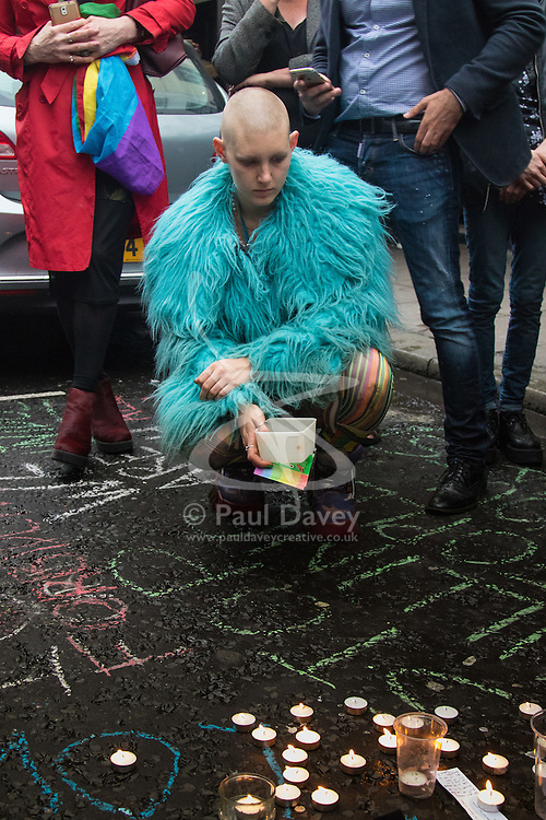 Old Compton Street, Soho, London, June 13th 2016. Thousands of LGBT people and their friends converge on Old Compton Street in London's Soho to remember the fifty lives lost in the attack on gay bar Pulse in Orlando, Florida. PICTURED: A mourner contemplates those lost after lighting a candle on Old Compton Street.