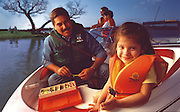 A family sits on a boat while fishing together in a big Texas lake