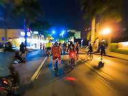 Cyclists in the March 28, 2014 Miami Critical Mass ride travel east on Calle Ocho (SW 8th Street) after dark.<br /> WATERMARKS WILL NOT APPEAR ON PRINTS OR LICENSED IMAGES.