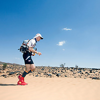 26 March 2007:  A participant runs across the beginning of dunes as the bivouac is at sight during the second stage (21.7 miles) of the 22nd Marathon des Sables between Khermou and jebel El Otfal. The Marathon des Sables is a 6 days and 151 miles endurance race with food self sufficiency across the Sahara Desert in Morocco. Each participant must carry his, or her, own backpack containing food, sleeping gear and other material.