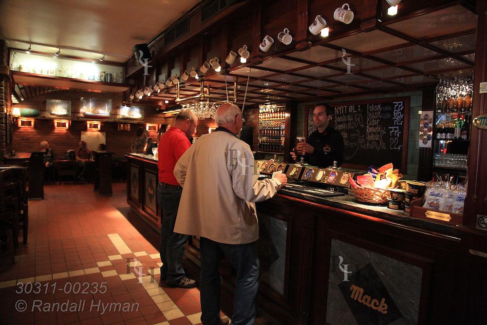 Patrons drink beer inside pub at Mack Brewery in downtown Tromso, Norway.