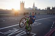 A youth balances on his rear wheel to perform a wheelie on the South side of Westminster Bridge, on 30th November 2016, in London England. Across the brdge, the sun sets behind the Houses of Parliament, currently undergoing major renovation works.