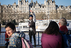 On the South Bank in London a busker entertains the public with a magic trick.