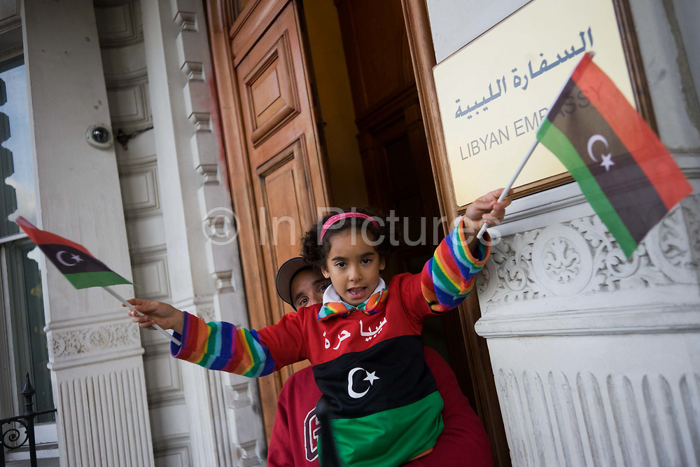 A young Libyan child whose grandfather was killed by the Gadaffi regime in 1979, celebrates by waving the revolutionary flag with her father outside their London embassy in Knightbridge, central London. Reacting to the death earlier in Sirte of the dictator Muammar Muhammad Abu Minyar al-Gaddafi, on the day his 42 year rule over Libya came to an official end.