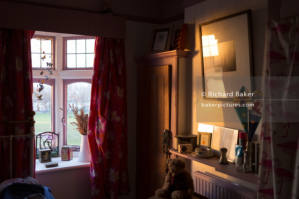 Late winter sunlight shines through a small first floor bay window and into a bedroom of an Edwardian period house, on 21st February 2019, in London, England.