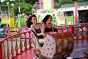 Young girls enjoying the rides at Adventure Island Funfair at Southend-on-sea, Essex. The town could be described as run down as while there are some signs of affluence, these are few and far between. The predominant atmosphere is quite rough feeling and quite poor. Southend is a seaside resort that is very popular with people from the East side of London due to it's close proximity, just an hour away by train along the Thames Gateway. With the decline of seaside resorts, from the 1960s much of the centre was developed for commerce and many of the original features were destroyed through redevelopment or neglect.