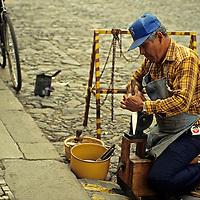 Central America, Guatemala, Antigua. A Guatemalan tradesman sharpens knives curbside in Antigua, Guatemala.
