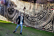 "Shangri La is a festival of contemporary performing arts held each year within Glastonbury Festival. The theme for the 2015 Shangri La was Protest.  Anonymous man poses in front of OBEY posters by Shepard Fairey in Shangri La<br /> Anonymous is a loosely associated international network of activist and hacktivist entities. A website nominally associated with the group describes it as ""an internet gathering"" with ""a very loose and decentralized command structure that operates on ideas rather than directives"". The group became known for a series of well-publicized publicity stunts and distributed denial-of-service (DDoS) attacks on government, religious, and corporate websites."
