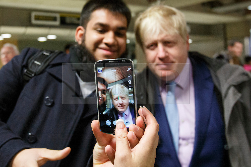 © licensed to London News Pictures. London, UK 05/02/2014. Mayor of Boris Johnson posing for a picture with a commuter before leaving London Bridge Underground Station on his way to City Hall during the 48 hour tube strike called by RMT Union on Wednesday, 5 February 2014. Photo credit: Tolga Akmen/LNP