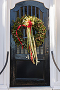 The wooden garden gate of a historic home decorated with a Christmas wreath on the Battery in Charleston, SC.