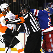 Ryan McDonagh, (right), Rangers, and Wayne Simmonds, Flyers, are separated by the referee during the New York Rangers Vs Philadelphia Flyers, NHL regular season game at Madison Square Garden, New York, USA. 26th March 2014. Photo Tim Clayton