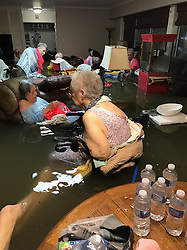 Aug 27, 2017 - Dickinson, Texas, U.S. - Residents at La Vita Bella nursing home in Dickinson Texas sit in flood waters as they wait to be rescued due to severe flooding from Hurricane Harvey. The residents were rescued Sunday. The dramatic photo went viral and circulated on the internet. (Credit Image: © Trudy Lampson/Twitter via ZUMA Wire)