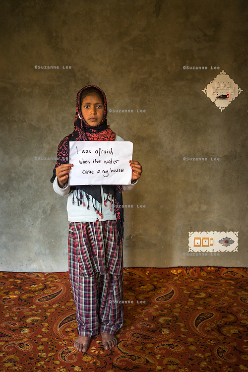 "Insha Majid, 12, holds a sign with the message ""I was afraid when water came in my house"" in her house, in Purnishadashah village, Jammu and Kashmir, India, on 24th March 2015. The floods happened at night when the banks of the Jhelum river broke, forcing flood-affected families to scramble for higher ground. Photo by Suzanne Lee for Save the Children"