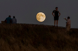 © Licensed to London News Pictures. 25/07/2018. LONDON, UK.  People watch the moon rise at Northala Fields in Northolt, West London, after another day when temperatures reached 30C.  On 27 July, a 'blood moon' is expected to be seen, with the moon appearing a reddish orange colour, during a lunar eclipse lasting one hour and 43 minutes.  Photo credit: Stephen Chung/LNP