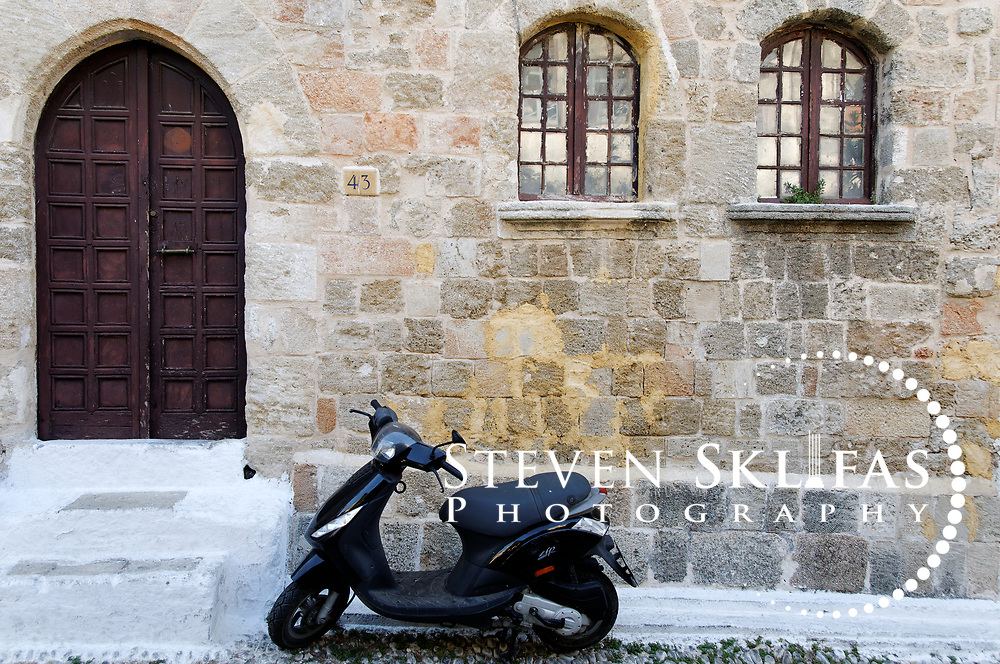 Rhodes. Greece. Picturesque view of a motor bike or scooter in front of an old stone building with an arched doorway and windows.